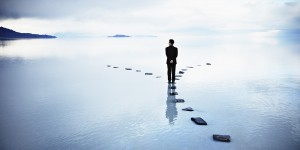 Businessman at fork of stone pathway in water